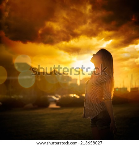 Silhouette of Young Woman at Urban Sunset. Dramatic Sky. Toned Instagram Styled Photo. - stock photo