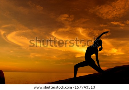 Silhouette of young woman doing yoga in sunrise at beach. - stock photo