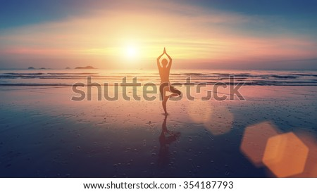 Silhouette of young woman practicing yoga on the beach at beautiful sunset. - stock photo