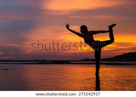 Silhouette of young woman practicing yoga on the lake at sunset - stock photo