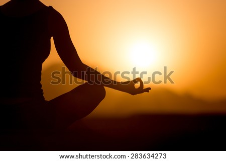 Silhouette of young woman sitting cross-legged with fingers in yogic Jnana mudra. Relaxation, meditation in beautiful mountainous landscape at sunset or sunrise, close up, copy space - stock photo