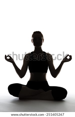 silhouette of young woman sitting on the floor doing yoga - stock photo