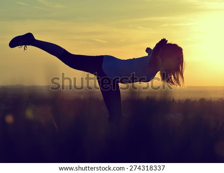 Silhouette of young woman stretching on a meadow at sunset - stock photo