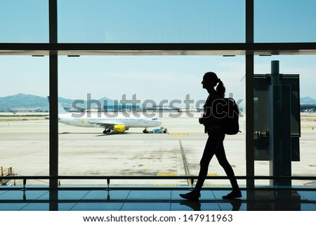 Silhouette of young woman walking at airport - stock photo