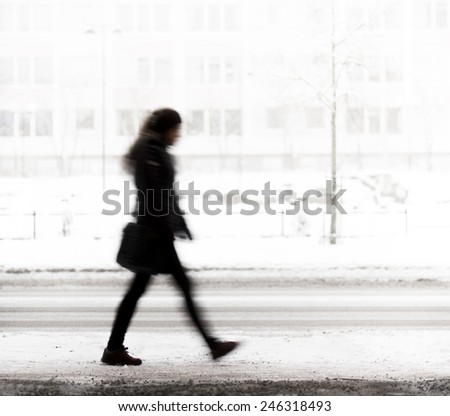 Silhouette of young woman walking on road in winter - stock photo