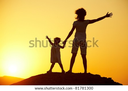 Silhouette of young woman with child against the bright sunset - stock photo