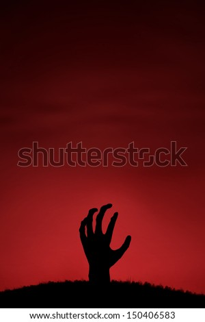 Silhouette of zombie hand coming up from the ground with copy space - stock photo