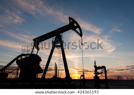 Silhouette oil pump jacks at sunset sky background. - stock photo