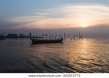 silhouette old boat sea sunset - stock photo