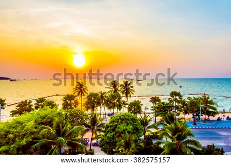 Silhouette palm trees on the beach with sunset - Vintage filter and boost up color processing - stock photo