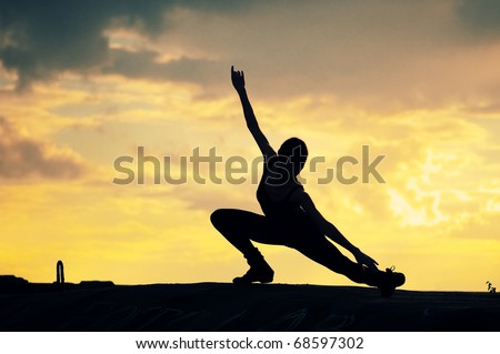 Silhouette photo of dancing woman in modern pilates style over sunset landscape. Yoga - stock photo