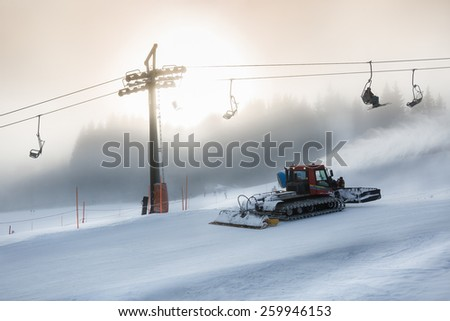 Silhouette photo of snow removal machine working on high ski slope at snowstorm - stock photo