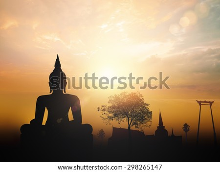 Silhouette public white Buddha, over golden autumn sunset background. Thailand travel concept. End of Buddhist Lent Day concept. - stock photo