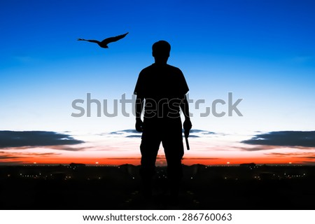 silhouette rear of man standing hand hold holding gun revolvers on sunrise and eagle fly on sky  in the city background - stock photo