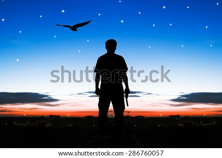 silhouette rear of man standing hand hold holding gun revolvers on sunrise and eagle fly on the sky in the city background - stock photo
