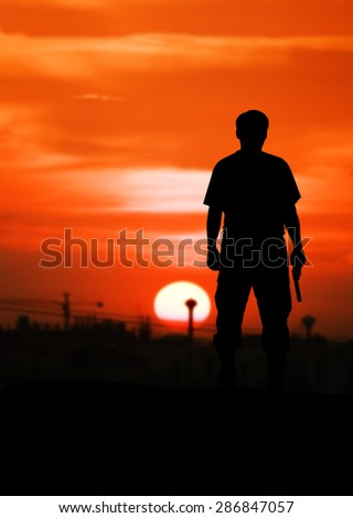 silhouette rear of man standing hand holding gun revolvers on sunset in the city background - stock photo