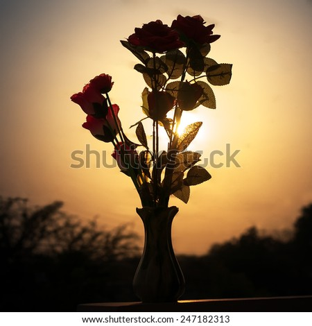 Silhouette red fake rose flowers in vase with sunlight - stock photo