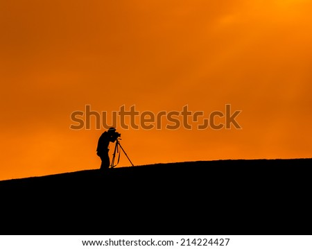 Silhouette shot of a photographer taking a photo over the hill - stock photo