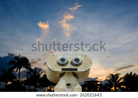 silhouette shot of coconut tree and sky in background with old binocular. - stock photo