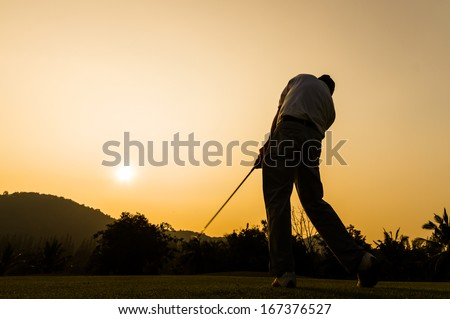 silhouette shot of golfer swing action - stock photo