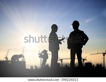Silhouette Successful male engineer standing survey work on construction over blurred Worker in  construction site over blurred nature. examination, inspection, survey - stock photo