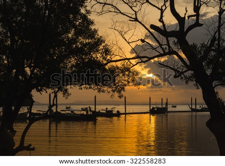 silhouette sunset at sea  with long tail boat - stock photo