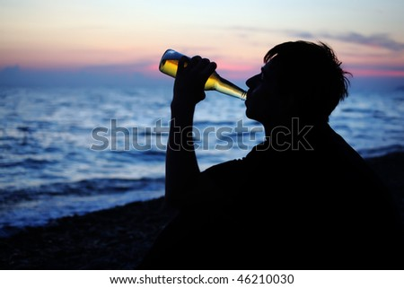 Silhouette teenager boy drinking beer on stone seacoast in evening - stock photo