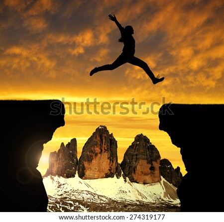 Silhouette the girl jumping over the gap at sunset in the background  Tre Cime di Lavaredo, Dolomite Alps, Italy - stock photo