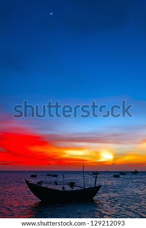 silhouette to the wooden fishing boat in the twilight of the red sun - stock photo