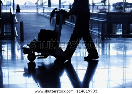 silhouette travelling peoples lifestyle in airport in black and white with blue tones - stock photo