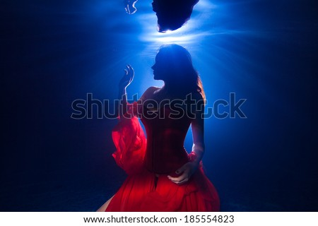 silhouette underwater photo pretty young girl  with dark long hair wearing red dress - stock photo