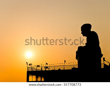 Silhouette view of Buddhist monk statue with twilight sun - stock photo