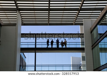 Silhouette view of some people in a modern office building interior with panoramic windows.  - stock photo