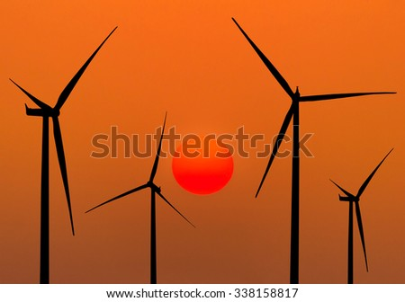 silhouette wind turbines generating electricity on sunset background  - stock photo