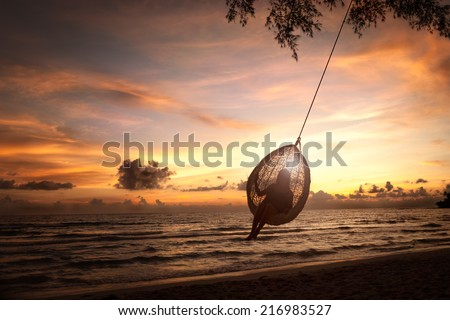 Silhouette woman on a beach swing - stock photo