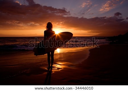 silhouette woman on tropical beach holding surfboard at sunset in maui - stock photo