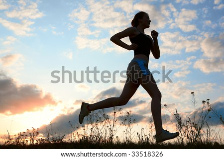 Silhouette woman run under blue sky with clouds and sun - stock photo