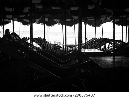 Silhouette wood beach chairs under umbrella. Black and white tone. Abstract background. - stock photo