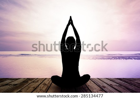 silhouette yoga practicing at sunset, meditation - stock photo