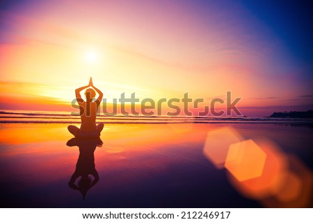 Silhouette yoga woman sitting on sea coast at beautiful surreal sunset. - stock photo
