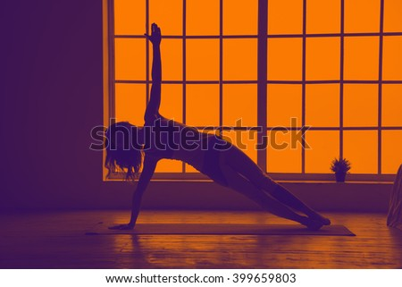 Silhouette yoga woman. Woman doing yoga fitness exercises near the window. Yoga. Fitness. Orange violet toning image. - stock photo