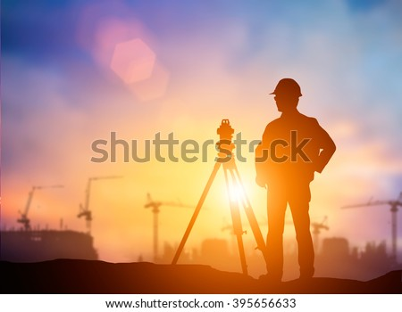 silhouette young engineer working construction standards in line with global construction environment and the environment around the work site. over Blurred construction worker on construction site - stock photo