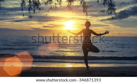Silhouette young female practicing yoga on beach at sunset. - stock photo