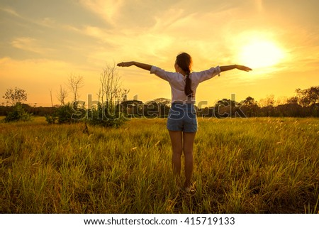 Silhouette Young happy woman in meadow  field on sunset. - stock photo