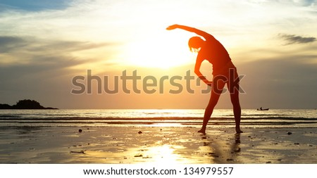 Silhouette young woman, exercise on the beach at sunset. - stock photo