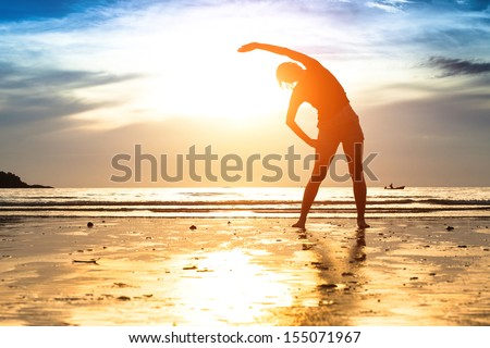 Silhouette young woman, exercise on the beach at sunset - stock photo