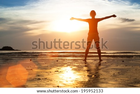 Silhouette young woman exercise on the ocean beach at sunset. - stock photo