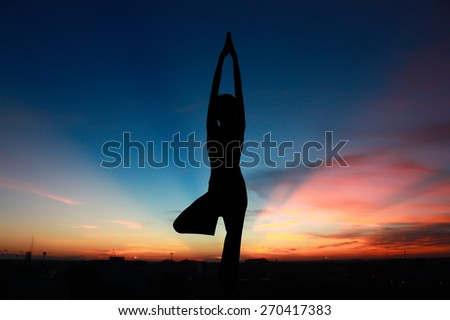Silhouette young woman practicing yoga on  sunrise in morning ,town view - stock photo