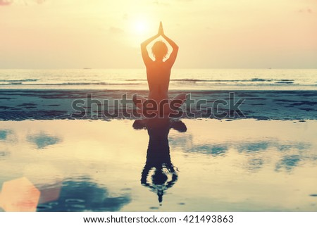 Silhouette young woman practicing yoga on the beach at amazing sunset. - stock photo