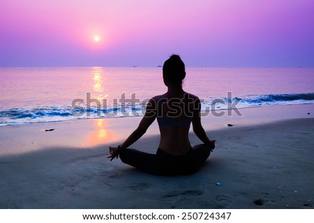 Silhouette young woman practicing yoga on the beach at sunrise - stock photo